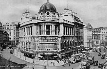 Black and white photograph of a large building with a domed-shape roof set on a corner plot on a busy London street.