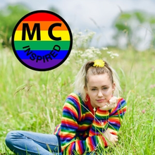 An image of a young woman wearing a rainbow-colored sweater and jeans. Her hair is pulled up in a ponytail with flowers. She is sitting in grassy field. There is a circle filled in by horizontal rainbow stripes. The letters
