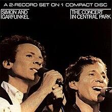 Een man met krullend haar, Art Garfunkel (links), en een kortere, glimlachende man, Paul Simon (rechts).