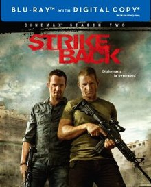"A blu-ray disc cover with a textured background and the title ""Strike Back"" in red letters on the top with the subtitle ""Diplomacy is overrated"" in white letters below. Below it are two men. The man on the left is stubbly with a blue shirt and holding a machine gun in his right hand. The man on the right is wearing a green T-shirt and holding a machine gun with both hands. Behind them is what appears to be smoke and buildings of some sort."