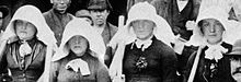 Four women wearing large white bonnets