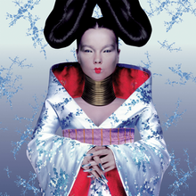 A picture of the album cover depicting a silver background with Björk standing facing forward in the middle. Björk is dressed in a outfit resembling a Kimono wearing large rings around her neck, silver fingernails and a large bun shaped hair style on each side of her head.