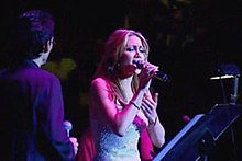 Woman singing on stage in pink lighting, with man next to her