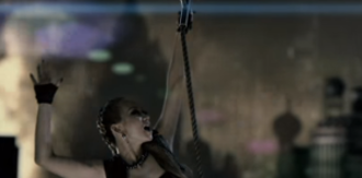 "Pop Diva - Still from the music video ""Pop Diva"", showing Koda hanging from a rope and being hauled away by an airship."