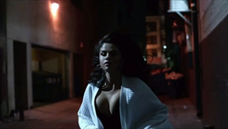 Selena Gomez running in a street at night dressed in an ivory sweater.