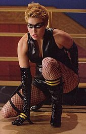A blonde woman sits crouched on one knee. She is wearing a black painted-on mask, with a black leather vest. She is also wearing black, elbow-length gloves, fishnet stockings, and knee-high black leather boots. The boots and gloves both have two gold, horizontal stripes. In the background is the railing to a staircase.