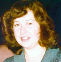 A slightly faded picture of a young woman with curly brown hair surrounding her slightly smiling face. She is dressed in a simple blue frock and has a simple necklace.