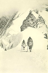 Photo of two men trudging out of a snowy, mountainous background