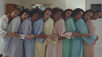 """New Rules (song) - Lipa (far left) and her on-screen friends on the music video for """"New Rules"""". The women are holding each other during the sleepover scene. The clip has been praised for its themes of female empowerment and friendship."""