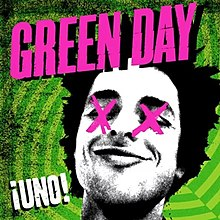 A black-and-white cutout of Billie Joe Armstrong's head, with his eyes crossed-out with pink X's, on a geometric, neon electric green background. The word