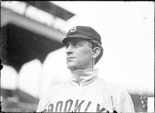 "A man wearing a baseball cap and jersey with ""Brooklyn"" written across the chest looks to the left."