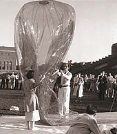 Woman in her thirties in a raincoat and man in his forties dressed in white holding a plastic balloon in front of observers, apparently in a stadium.