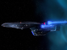 An oblong, blue-grey starship with an oval hull and two flanking, glowing engines