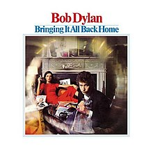 A photograph of Dylan staring at the camera with a woman reclining behind him on a chair. A lens effect blurs the edges of the photo.