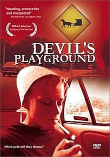 Red-tinted DVD cover with the film title featuring a girl in white Amish-style bonnet and dark plain dress, seated in the back seat of a car, lighting a cigarette.
