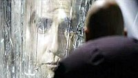 The face of a man appears in a crystalline wall, while a bald man with his back at the camera looks at him.