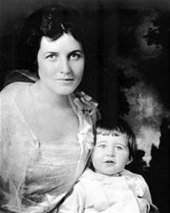 Waist high portrait of woman in her twenties with a child in front of her
