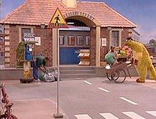 Television set, showing a large brick building on a city street; to the right, a large puppet is pushing a wheelbarrow and to the left, a man, next to a phone booth, is bending over several mail bags. Closer to the front of the image is a signpost, with a triangle that has a black figure and a yellow background, on top.