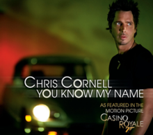 "A man stands in front of an out-of-focus sports car. The background is a gradient that goes from red to green. Besides the man is written ""Chris Cornell"", with ""You Know My Name"" below it. In the down right corner is the text ""As featured in the motion picture CasinO ROyale"", with a gun-like ""7"" below Royale's ""O""."