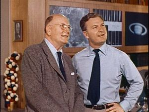 Photograph of two men standing. The man on the left is wearing a suit and tie; he is middle-aged, wears eyeglasses, and is bald. The man on the right is wearing a loose tie and is much younger. Behind the two men is a wood-paneled wall with photographs, one of which is the planet Saturn. There is also a large model of a molecule behind them, possibly illustrating DNA.