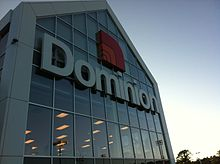 A photograph of the Dominion Store exterior, framed to show the logo.