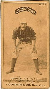 A baseball player standing facing the camera with his hands resting on his knees