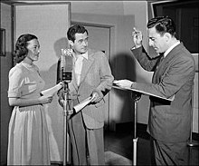 Two men and a woman in radio studio, one man directing the other two