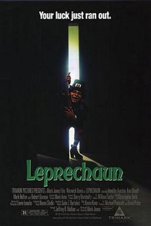 Actor Warwick Davis, dressed in heavy make-up as a leprechaun, opens a door and lights up a dark room