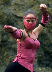 This image shows a masked woman with braided black hair, in a martial arts pose, wearing an a pink-and-black outfit.