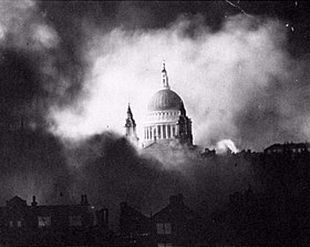 Black and White photograph of the dome of St Paul's, starkly lit, appearing through billowing clouds of smoke