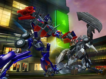 Screenshot of Wii gameplay, showing Optimus Prime attacking an unknown Decepticon. A stylized Shanghai street fills in the background.