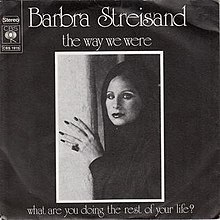 In this black-and-white photograph, Barbra Streisand appears wearing a shawl around her head with her hand against a wall.