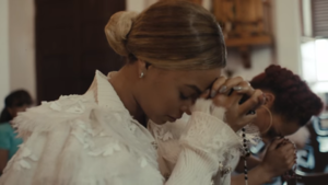 "Heaven (Beyoncé song) - A still from the music video for ""Heaven"" in which Beyoncé is seen together with Ashley Everett. In the scenes where the two are seen together praying at the church, Everett has already died and Beyoncé mourns her."