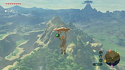 An in-game screenshot of the protagonist Link, paragliding across a vast world.