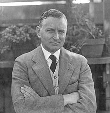 Man in a light-colored suit with crossed arms looking at the camera