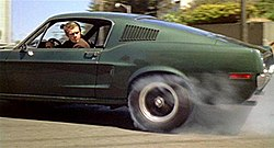 Photograph of a car with a driver looking backwards out of its window. The car's rear tire is smoking because it is spinning against the road.