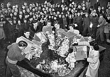 Photo of men and women burning boxes of comics in a bin as a crowd of children watch.