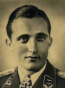 The head and shoulders of a young man, shown in semi-profile. He wears a military uniform with an Iron Cross displayed at the front of his white shirt collar.