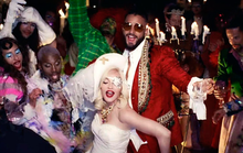 Image of several people at a party. On the left, there are people wearing colorful make-up and outfits as a woman and a man stand out on the middle; the woman wears a white dress, a hat and an eye-patch, while the man wears a red suit and glasses. Other people appear on their back as candles are also featured.
