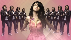 "Naturally (Selena Gomez & the Scene song) - A screenshot of Gomez and band member Ethan Roberts back dropped by colorful background in the music video of ""Naturally""."
