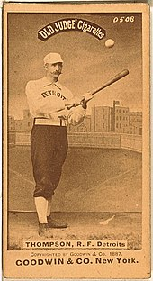 A sepia-toned baseball card image of a man wearing an old-style white baseball uniform and cap