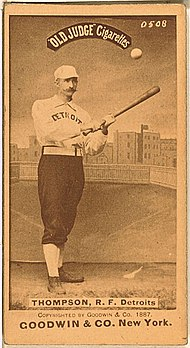 A sepia-toned image of a mustachioed man wearing an old-style baseball uniform holding a baseball bat
