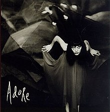 A black-and-white photo of a Caucasian woman leaning forward while holding the ends of a flowing black dress In the corner Adore is displayed in white handwriting