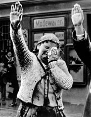 Cropped image of what first appeared in the Nazi party newspaper Völkischer Beobachter, ostensibly depicting a Sudeten German woman in Asch crying tears of joy when Hitler crossed the border in 1938. Allied propaganda later used the cropped image with other interpretations.