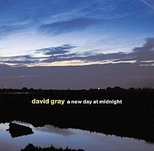 A photograph of a sunrise over a body of water with the artist and album title overlaid