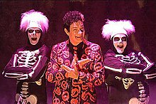 7c27c7c0 David S. Pumpkins. Saturday Night Live character. a man in an orange suit  pointing to two flanking skeletons