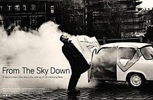 "A black-and-white image of Larry Mullen, Jr. in front of a large cloud of smoke coming from a car. He is staring upwards with his body arched backward. The title ""From the Sky Down"" is written on the left, with film credits below."