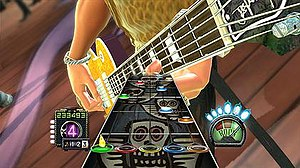 Guitar Hero: Aerosmith - To play the game, players must use a guitar peripheral to play the scrolling notes. Players must hold a colored fret on the peripheral corresponding to the on-screen note and then press the peripheral's strum bar as the note crosses the target.