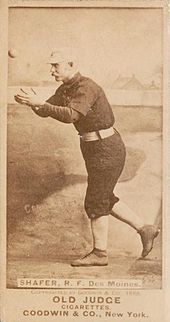 A man in a baseball uniform has his arm out in front of body attempting to catch a baseball.
