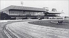 Picture of Rosecroft's track and old grandstand. A horse is racing on the track. To the right, there are several rows of bleachers with a metal tent above for protection.